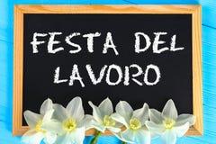 Svart tavla med texten i italienare: Arbets- dag Vita blommor av påskliljor på en blå trätabell Arbets- dag och vår, Maj 1 Arkivfoto
