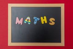 Svart svart tavla med träramen, ord, textmatematik i färgrika bokstäver, röd väggbakgrund royaltyfri bild