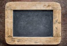 Svart tavla med träramen, svart tavla på gammal wood bakgrund arkivbilder
