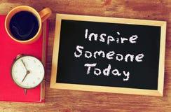 Svart tavla med uttrycket inspirerar någon i dag som är skriftligt på den över trätabellen med kaffe och tappningklockan Arkivbild