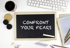 Svart tavla på kontorsskrivbordet med text: Konfrontera dina skräck Arkivfoton