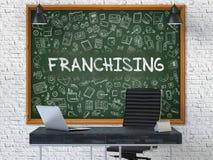 Svart tavla på kontorsväggen med att bevilja franchise begrepp 3d Arkivbilder