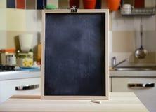 Svart tavla på trätabellen på kökbakgrund Royaltyfria Bilder