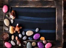 Svart tavla som dekoreras med havet, anmärker formade godisar och kiselstenar Arkivfoton