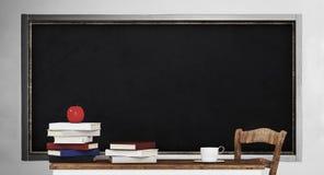 Svart tavla, tabell, hög av böcker och äpple, i klassrum Arkivbild