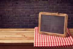 Svart tavlabakgrund med den röda kontrollerade bordduken över den svarta tegelstenväggen Royaltyfri Bild