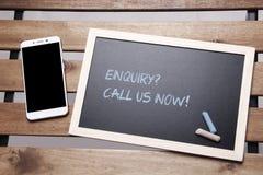 Svart tavlabegrepp med mobiltelefonen: kalla oss nu Royaltyfri Fotografi