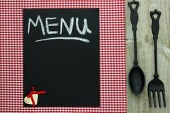 Svart tavlamenytecken på röd rutig bordduk med den gjutjärnskeden och gaffeln Arkivbild
