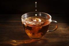 Svart te bryggade nytt i en glass kopp, och några droppar av mjölkar nolla Arkivfoto