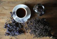 Svart te eller kaffe i en vit kopp på ett bräde med torkade örter royaltyfri bild