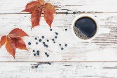 Svart te i den vita porslinkoppen på tappningträtabellen Royaltyfria Foton