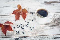 Svart te i den vita porslinkoppen på tappningträtabellen Royaltyfri Foto