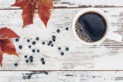 Svart te i den vita porslinkoppen på tappningträtabellen Arkivbild