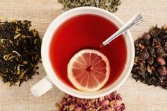 Svart te i en sked Arkivfoton