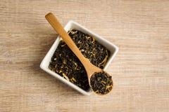 Svart te i en sked Arkivbild