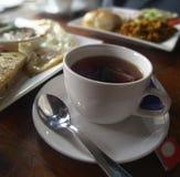Svart te i en vit kopp på frukosttabellen royaltyfria bilder