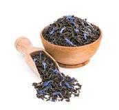 Svart te med blåa kronblad i en träbunke som isoleras på vit Arkivbilder