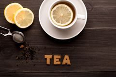 Svart te med citronen och kakate på en träbakgrund royaltyfria bilder