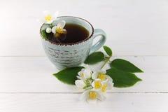 Svart te med jasmin på en vit tabell Royaltyfri Fotografi