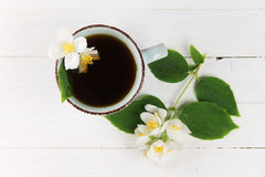 Svart te med jasmin på en vit tabell Royaltyfri Bild