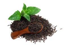 Svart te med mintkaramellen och en träsked Arkivfoto