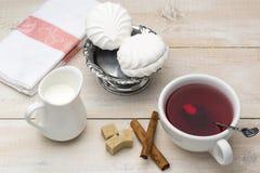 Svart te med mjölkar Rottingsocker och kanelbruna pinnar Arkivfoton