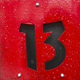 Svart tecken för nummer tretton på en röd metallplatta Royaltyfri Bild