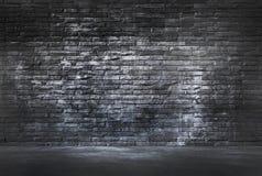 Svart tegelstenvägg och cementgolv Arkivbild