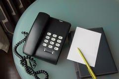 Svart telefon med den pappers- anmärkningen, kommunikation Arkivfoton