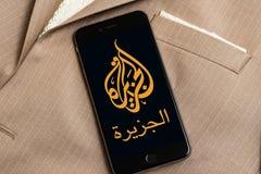 Svart telefon med logo av nyhetsmedia Al Jazeera på skärmen royaltyfri foto