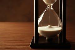 Svart timglas med vit sand på bakgrund royaltyfria bilder