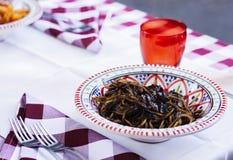 Svart tioarmad bläckfiskfärgpulverpasta på plattan med denblått modellen i restaurangen av Catania, Sicilien, Italien royaltyfria foton
