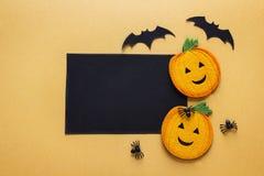 Svart tomt pappers- kort med det dekorativa pumpor, spindlar och slagträet royaltyfria foton