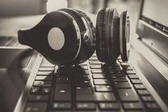 Svart trådlös dobbel eller Deejay Headset Lying On ett anteckningsboktangentbord med litet överexponerade monokromfärger fotografering för bildbyråer