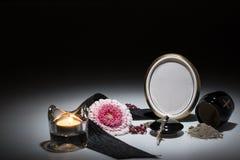 Svart urna med det svarta bandet, gerberablomma, stearinljus, radband för sy Royaltyfri Foto