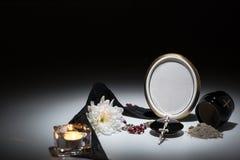 Svart urna med det svarta bandet, krysantemum, stearinljus, radband för symp Arkivbild