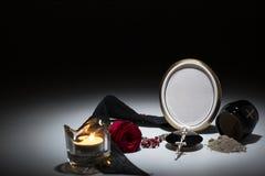 Svart urna med det svarta bandet, röd ros, stearinljus, radband för sympati Arkivfoton