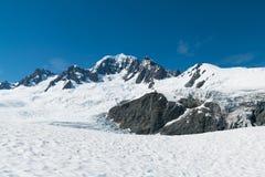 Svart vaggar berget med bakgrund för snö och för blå himmel royaltyfri foto