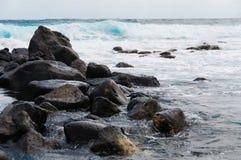Svart vaggar stenkusten framme av det grova blåsiga havet fotografering för bildbyråer