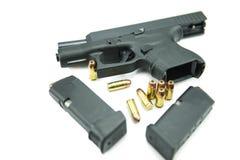 Svart vapen och 9mm kulor en vit bakgrund Arkivbild