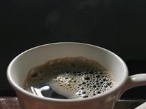 Svart varmt kaffe med bubblor och skum i koppslut upp på trätabellen arkivbilder