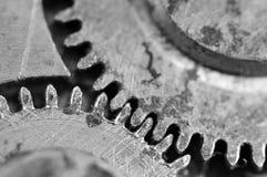 Svart vit bakgrund med metallkugghjul ett gammalt urverk Arkivfoto