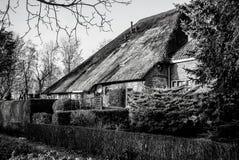 Svart-vit foto av det gamla hemtrevliga huset med det halmtäckte taket Arkivfoto