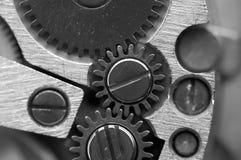 Svart vit metallisk bakgrund med metallkugghjul ett urverk Arkivfoto