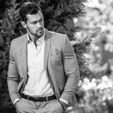 Svart-vit poserar den utomhus- ståenden av den eleganta stiliga mannen i klassisk grå färgdräkt utomhus- Arkivfoton