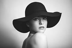Svart vit stående av kvinnan i svart hatt Arkivfoton