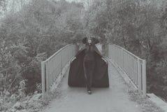 svart white Flickan i maskeringen och ansvar av bron på vägen till allhelgonaaftonen royaltyfria bilder