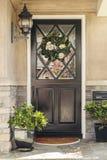 Svart ytterdörr som returnerar med blommakransen Royaltyfri Foto