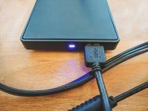 Svart yttre hårddisk som förbinder in i usb-kabel Arkivbild
