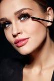 svarta ögonfranser long Kvinna med makeup som applicerar skönhetsmedel royaltyfria bilder